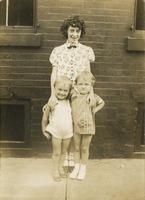 Teenage girl standing with two little girls in front of brick house, Philadelphia.
