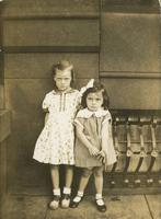 Two little girls standing in front of a stone building, Philadelphia.
