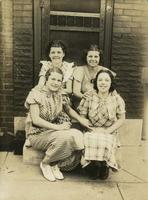 Four young women sitting on marble stoop, Philadelphia.