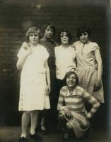 Five young female friends standing in front of a brick wall, Philadelphia.