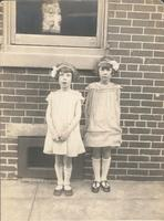 Two girls standing in front of window, Philadelphia.