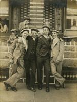 Four teenage boys standing in front of brick and stone house, Philadelphia.