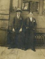 Two young men in three-piece suits standing in front of brick and brownstone house, Philadelphia.