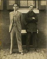 Two men, possibly father and son, standing in front of brick house, Philadelphia.
