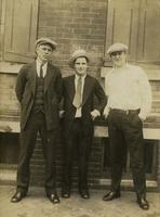 Three men standing outside a brick house, Philadelphia.