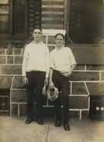Two young men with caps in their hands standing in front of stone porch, Philadelphia.