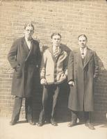 Three young men standing in front of brick wall, Philadelphia.