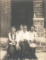 Four men sitting on stone step in front of porch, Philadelphia.