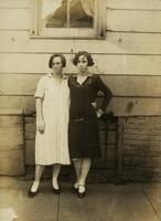 Two women standing in front of old house, Philadelphia.