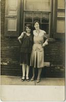 Two women standing in front of brick house, Philadelphia.