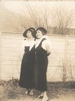 Two women standing in front of tall wooden fence, Philadelphia.