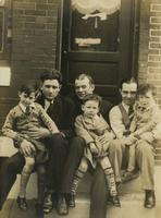 Three men, possibly fathers, with three boys, possibly their sons, sitting on marble step, Philadelphia.