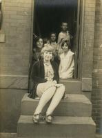 Two teenage girls and four younger children sitting at doorway of row house, Philadelphia.