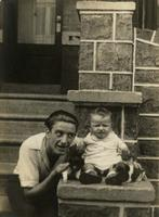 Man, baby boy, and two puppies on a stone porch, Philadelphia.