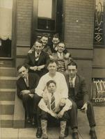 Seven men and a young boy sitting on brownstone steps, Philadelphia.