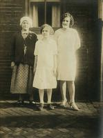 Three females standing in front of brick house, Philadelphia.