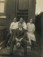 Three men and a woman on stone steps next to an alley, Philadelphia.