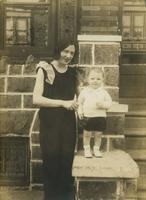 Young woman standing on porch with little boy, Philadelphia.