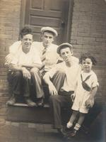 Three men and a little boy sitting on a wooden stoop, Philadelphia.