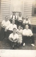 Seven men and one woman sitting on the steps of a wooden house, Philadelphia.