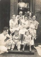 Group of fourteen people sitting and standing in the doorway of a brick house, Philadelphia.