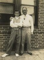 Man and teenage boy standing in front of a brick house, Philadelphia.