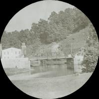 [View of canal bridge with adjacent mill building.]