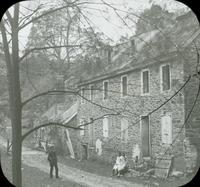 [Man and two girls in front of the old Livezey mill on the Wissahickon Creek, Philadelphia.]