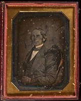 [Portrait of an unidentified man seated facing right, with his hands folded in his lap.]